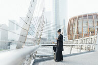 Businesswoman with trolley luggage on pedestrian bridge, Milan, Italy - ISF05967