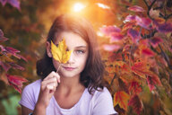 Portrait of young girl in rural setting, holding leaf in front of eye - ISF06018