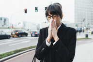 Businesswoman blowing nose on busy road, Milan, Italy - ISF06108