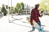 Cool young man with skateboard walking in the city, using smartphone - UUF13850