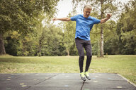 Full length front view of senior man in park jumping in mid air - CUF13215