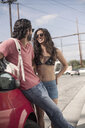 Young couple chatting whilst leaning against red car at roadside, Los Angeles, California, USA - CUF13248