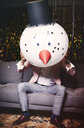 Man sitting on sofa at party, holding snowman head in front of face - ISF06134