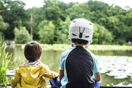 Two young brothers sitting at water's edge, older brother wearing cycling helmet, rear view - ISF06182