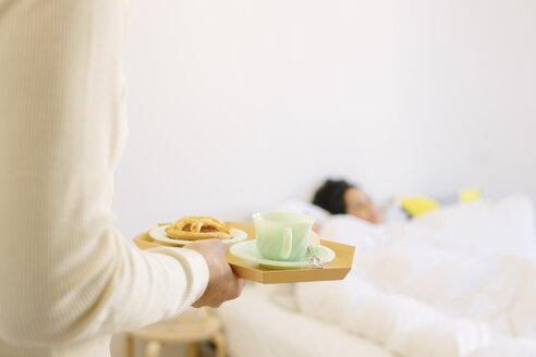 Cropped shot of young man serving girlfriend breakfast in bed - CUF13327