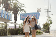 Female friends walking past motel, Los Angeles, California, USA - CUF13380