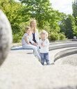 Mother and her little daughters spending time together in a park - CVF00621