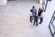 High angle view of businesswoman and men having discussion in office atrium - CUF13554