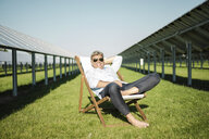 Mature man sitting in beach lounger, solar plant - MOEF01120