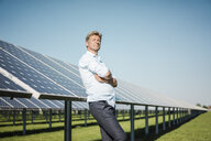 Mature man with closed eyes leaning on solar panel - MOEF01129