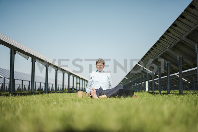 Mature man sitting barefoot on meadow, laptop and coffee to go cup, solar plant - MOEF01141