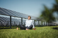 Mature man sitting barefoot on meadow, laptop and coffee to go cup, solar plant - MOEF01144