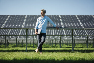 Mature man with laptop standing barefoot on meadow, solar plant - MOEF01147