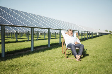 Smiling mature man sitting in sun lounger, solar plant - MOEF01150