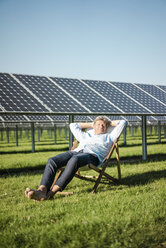 Mature man sitting in sun lounger, solar plant - MOEF01153