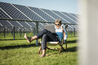 Mature man sitting in beach lounger, using laptop in solar plant - MOEF01156