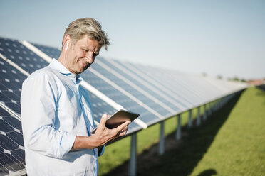 Businessman using tablet at solar park - MOEF01159