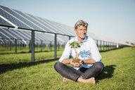 Mature man holding privet, solar plant - MOEF01168