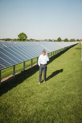 Businessman using smartphone at solar park - MOEF01171