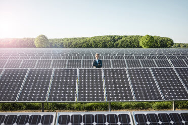 Mature man standing on panel in solar plant - MOEF01174