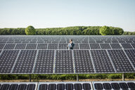 Mature man using smartphone standing on panel in solar plant - MOEF01177
