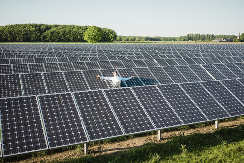 Mature man resting on panel in solar plant - MOEF01180