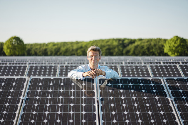 Smailing mature man standing in solar plant - MOEF01183