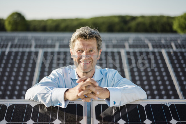Smiling mature man standing in solar plant - MOEF01186