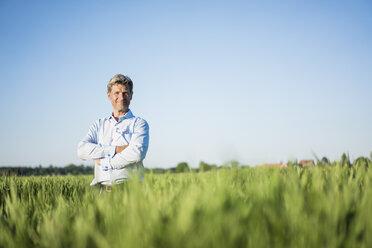 Businessman standing in grain field, arms crossed - MOEF01195