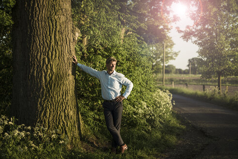 Businessman standing on tree - MOEF01201