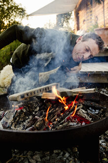 Mature man leaning to inspect fire pit - CUF13724