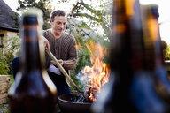 Mature man using stick to poke fire pit - CUF13730