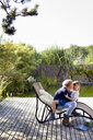 Mother and daughter hugging on lounge chair on decking - CUF13745