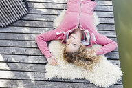 Young woman lying on furry rug on decking, high angle - CUF13748