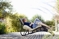 Mid adult woman relaxing on lounge chair on wooden decking - CUF13766