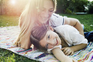 Mother and daughter lying on rug in garden - CUF13799