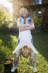 Mother lifting daughter upside down in garden - CUF13802
