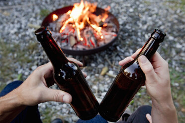 Hands holding beer bottles with campfire - CUF13808