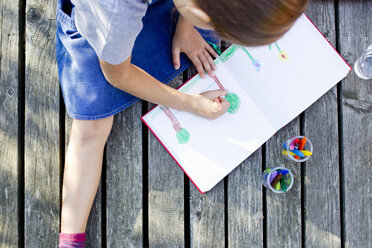 Girl drawing picture in notebook, high angle - CUF13817