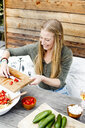 Woman scarping tomatoes into bowl from chopping board - CUF13826
