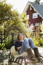 Mid adult woman relaxing on lounge chair on wooden decking - CUF13832