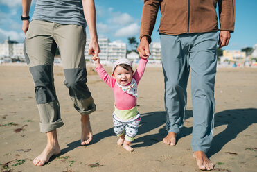 France, La Baule, portrait of happy baby girl walking on the beach with father and grandfather - GEMF02013