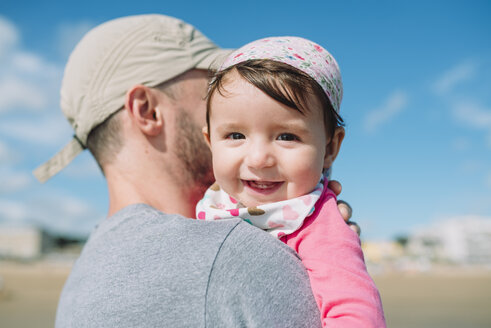 Portrait of happy baby girl on father's arms on the beach - GEMF02016
