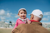 France, La Baule, portrait of baby girl on grandfather's arms on the beach - GEMF02019