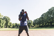 Young Afro-American man training boxing on sports field, outdoors - UUF13868