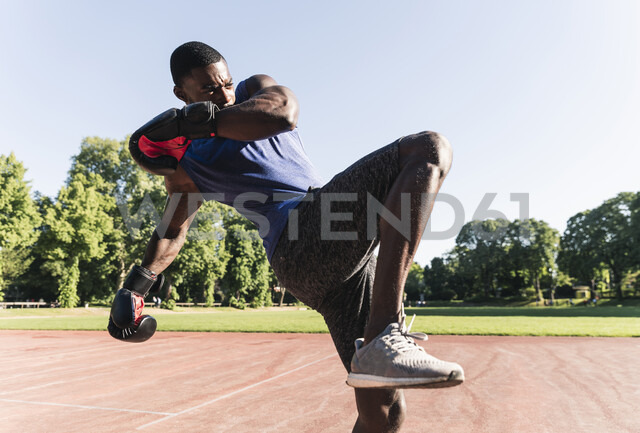 Young Afro-American man training boxing on sports field, outdoors - UUF13871