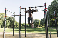 Muscular young man exercising on parcours bars - UUF13880