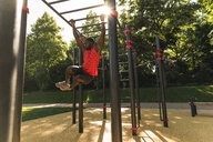 Muscular young man exercising on parcours bars - UUF13883