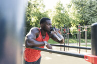Young athlete training on parallel bars, outdoors, drinking water - UUF13886