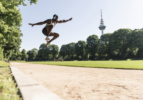 Young athlete with headphones, listening music, training long jump - UUF13904